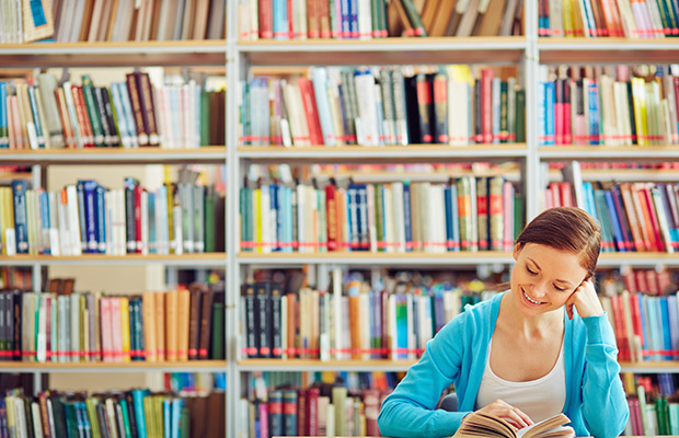 Student sitting in the library in front of bookshelves