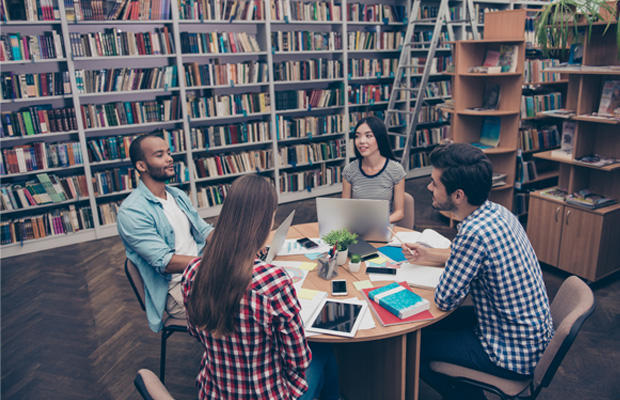 four students working in library