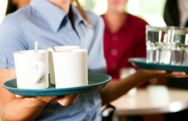 Waitress holding trays of drinks