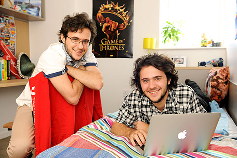 Two students relax in one of their rooms