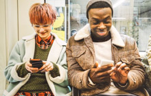 Students laughing together using phones