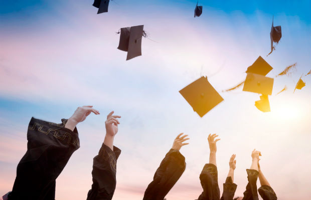 Graduates throwing hats in air