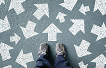 feet standing on floor covered with arrows