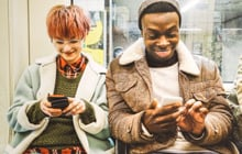 Students laughing while using mobile phones