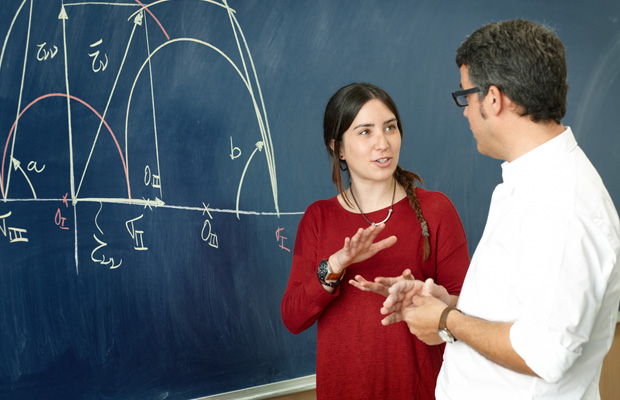 student and professor talking in front of a chalkboard