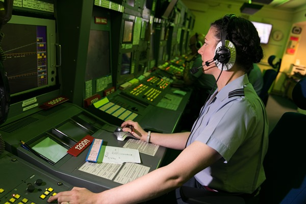 RAF Air Ops Controller at a bank of desks with monitors