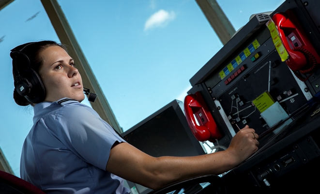 Air Ops Controller at control desk in front of large windows