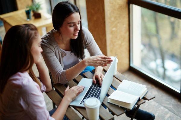 Girls studying using laptops