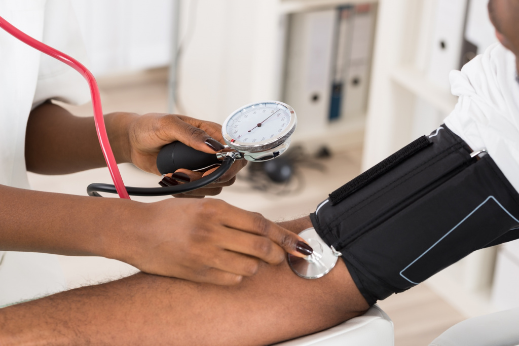 A medical professional taking a blood pressure reading from a patient