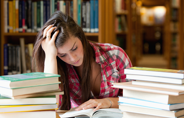 student surrounded by books