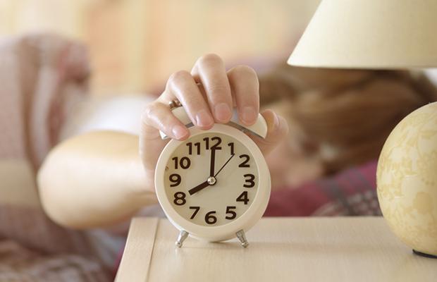 someone turning off their alarm clock