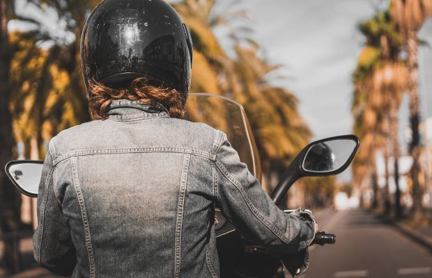 A teenage girl riding a moped