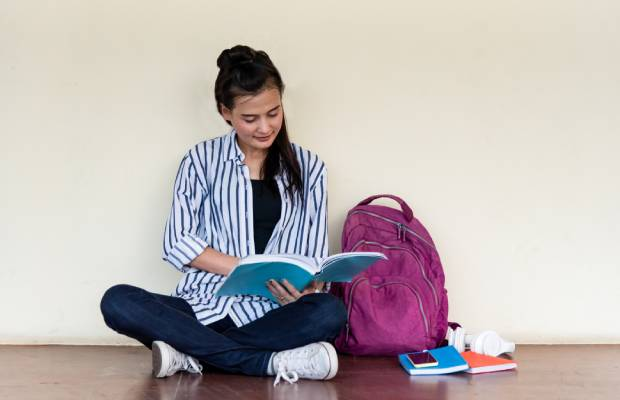 Young student revises with backpack and notebook