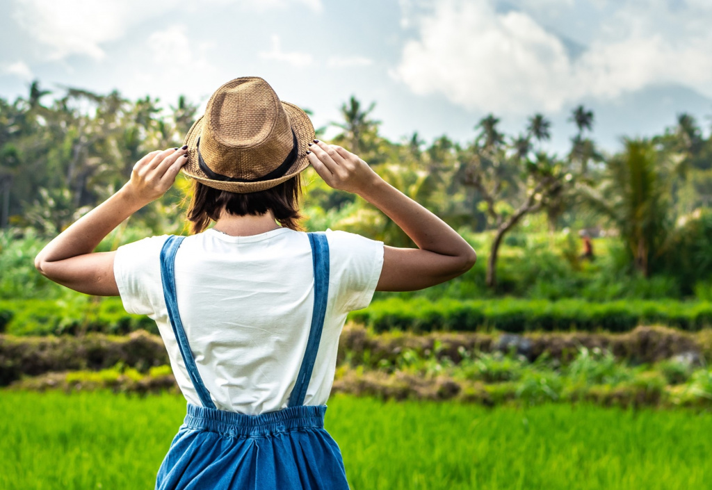 Woman sat with back to camera in tropical location