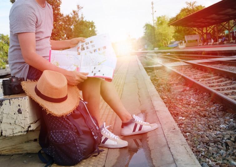 Man sat at railway station, reading a map