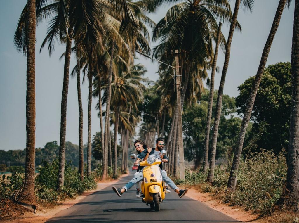Couple on motorcycle among coconut trees