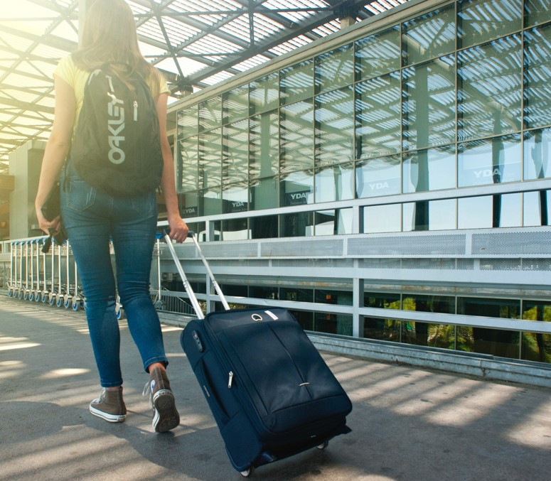 Woman arriving with luggage to airport