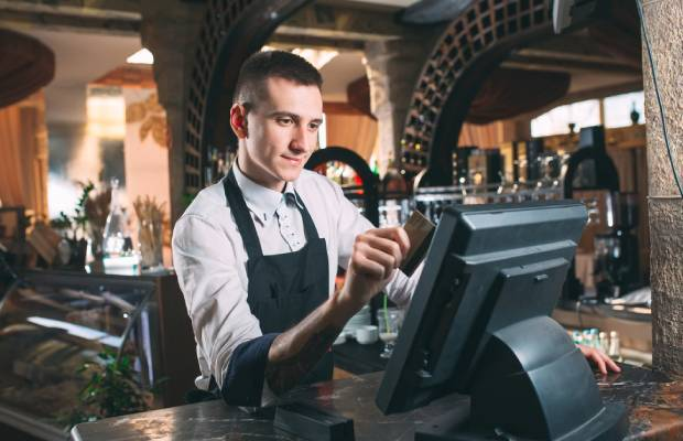 Waiter at till in restaurant