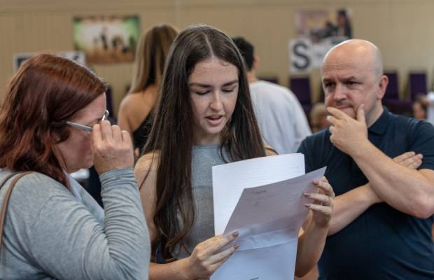 Student looks at 2019 GCSE results with parents