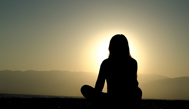 Silhouette of a woman from the back, sat crosslegged in front of a sunset