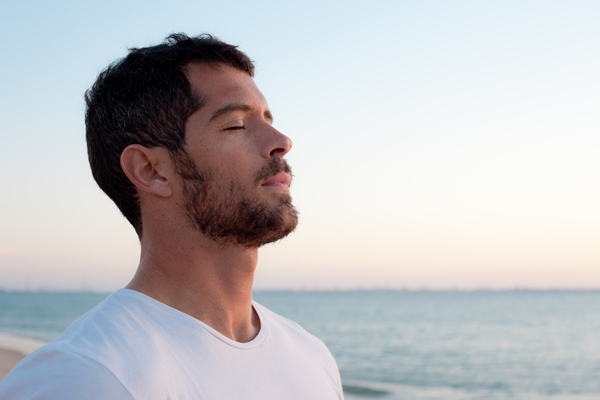 Man in white t-shirt deep breathing in front of ocean