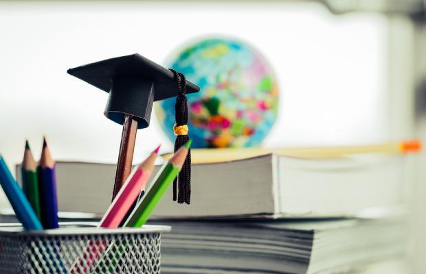 pot of pencils including a pen with a graduate hat topper