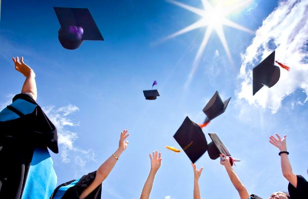 university graduates throwing hats in the air