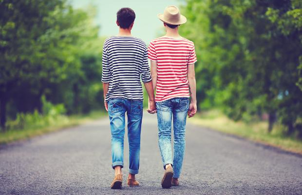 two teenage boys holding hands while walking through park