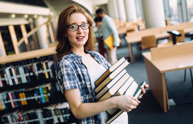 student holding pile of books in library