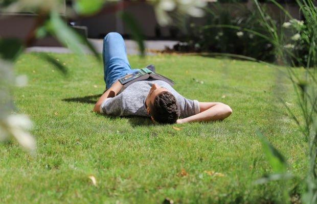 teenager lying in park with book