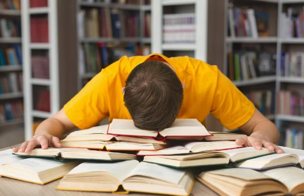 teenager lying face-down on pile of books