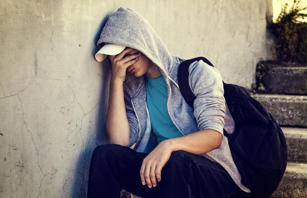 teenager sitting on steps with head in hands