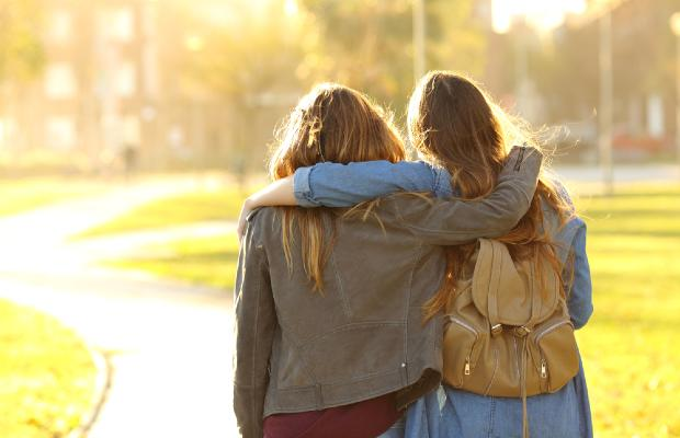 teenage girls walking with arms around each other