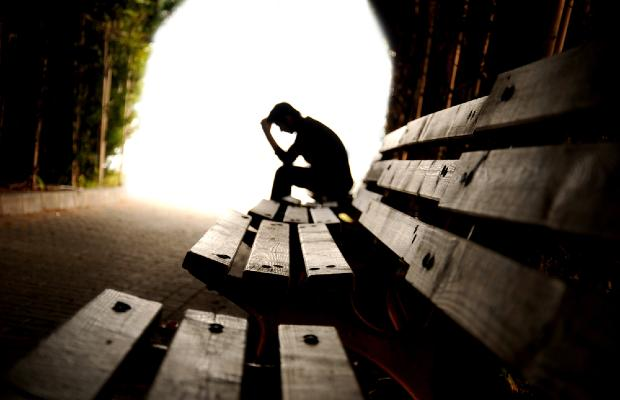teenager sitting on bench with head in hands