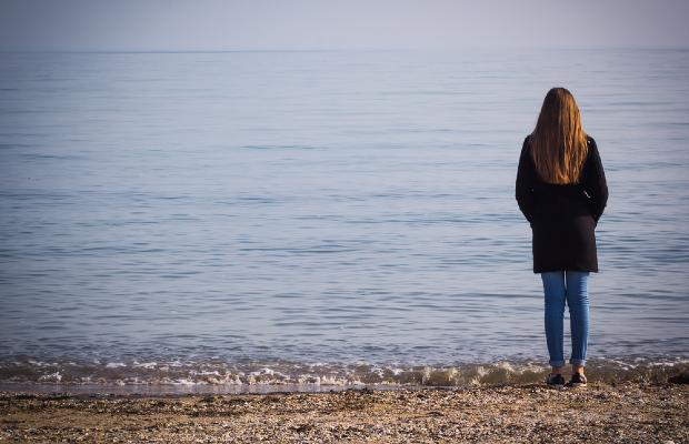 teenager standing alone on beach