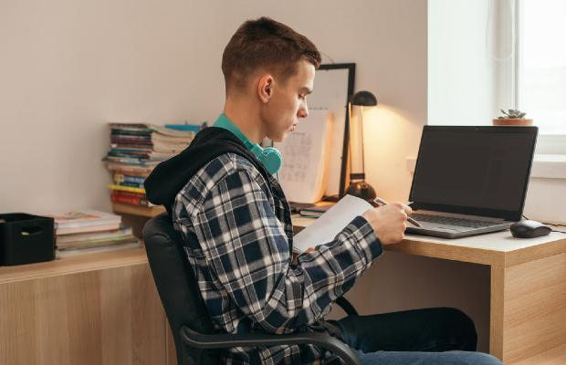 teenager studying at desk at home