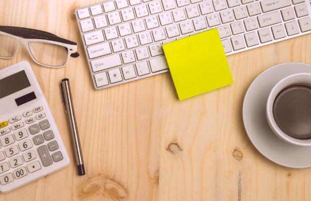 coffee, calculator and keyboard on desk