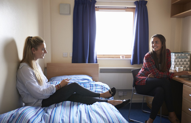 two students chatting in bedroom
