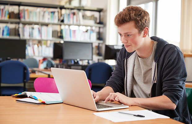 happy student looking at laptop