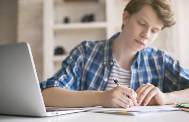 Boy takes notes while studying with laptop open