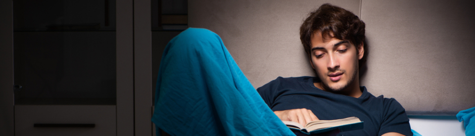 Young man lying in bed reading
