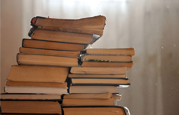 pile of yellowed books in a dusty room