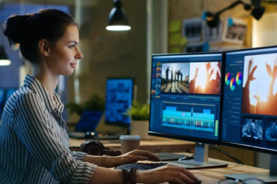 young woman working on computer screens