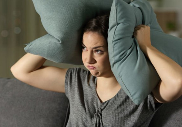 Angry woman covering ears with cushions