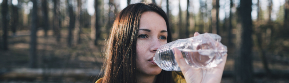 Young woman drinking water on woodland walk