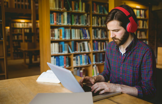 Student listening to headphones on laptop