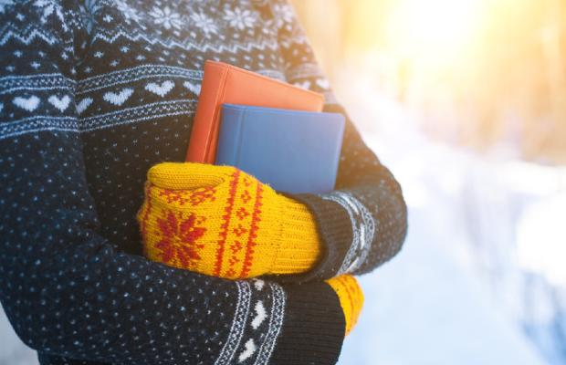 girl wearing gloves and jumper and holding books