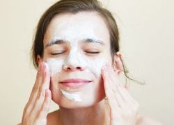 Young woman using exfoliator on her face