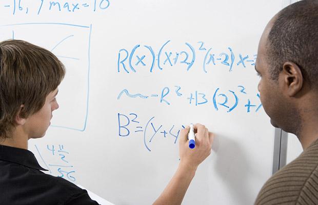 student working on maths problem as teacher looks on