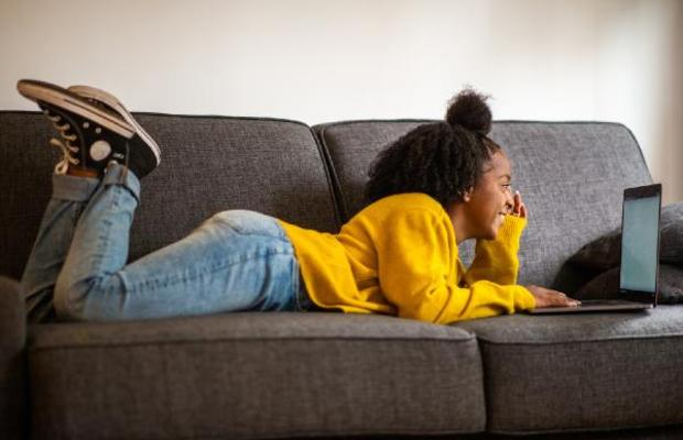 student lying on sofa with laptop